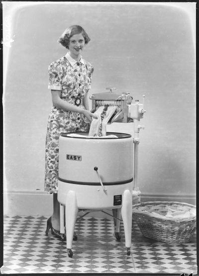 Woman using wringer washing machine