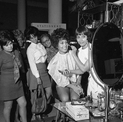Flori Roberts Cosmetics makeup artist demonstrating products to women, Los Angeles, 1970.